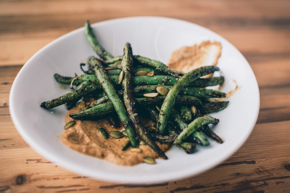 Blackened green beans with burnt onion aioli and pepitas / Photo x Colin Gordon